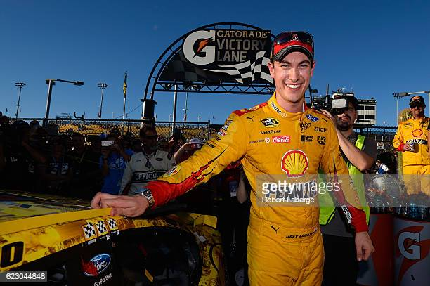 Joey Logano driver of the Shell Pennzoil Ford poses with the winner's decal on his car in Victory Lane after winning the NASCAR Sprint Cup Series...