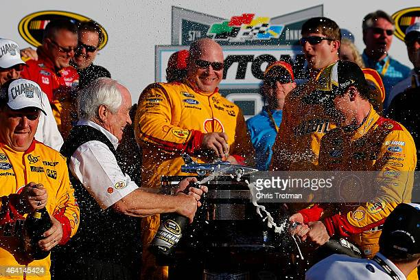 Joey Logano driver of the Shell Pennzoil Ford right and team owner Roger Penske celebrate in victory lane with champagne after winning the NASCAR...