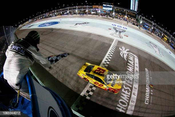 Joey Logano driver of the Shell Pennzoil Ford takes the checkered flag to win the Monster Energy NASCAR Cup Series Ford EcoBoost 400 and the Monster...
