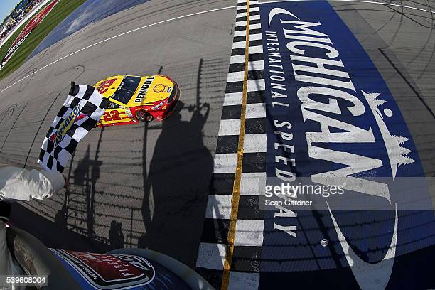 Joey Logano driver of the Shell Pennzoil Ford takes the checkered flag to win the NASCAR Sprint Cup Series FireKeepers Casino 400 at Michigan...
