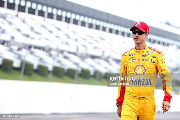 Joey Logano driver of the Shell Pennzoil Ford walks down pit road during qualifying for the NASCAR Sprint Cup Series Axalta 'We Paint Winners' 400 at...