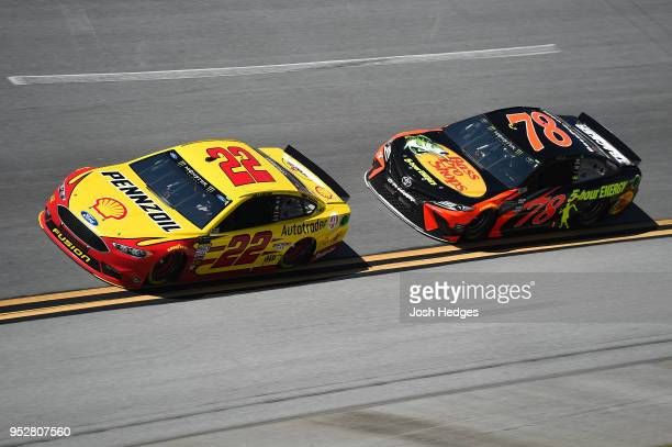 Joey Logano driver of the Shell Pennzoil/Autotrader Ford leads Martin Truex Jr driver of the Bass Pro Shops/5hour ENERGY Toyota during the Monster...