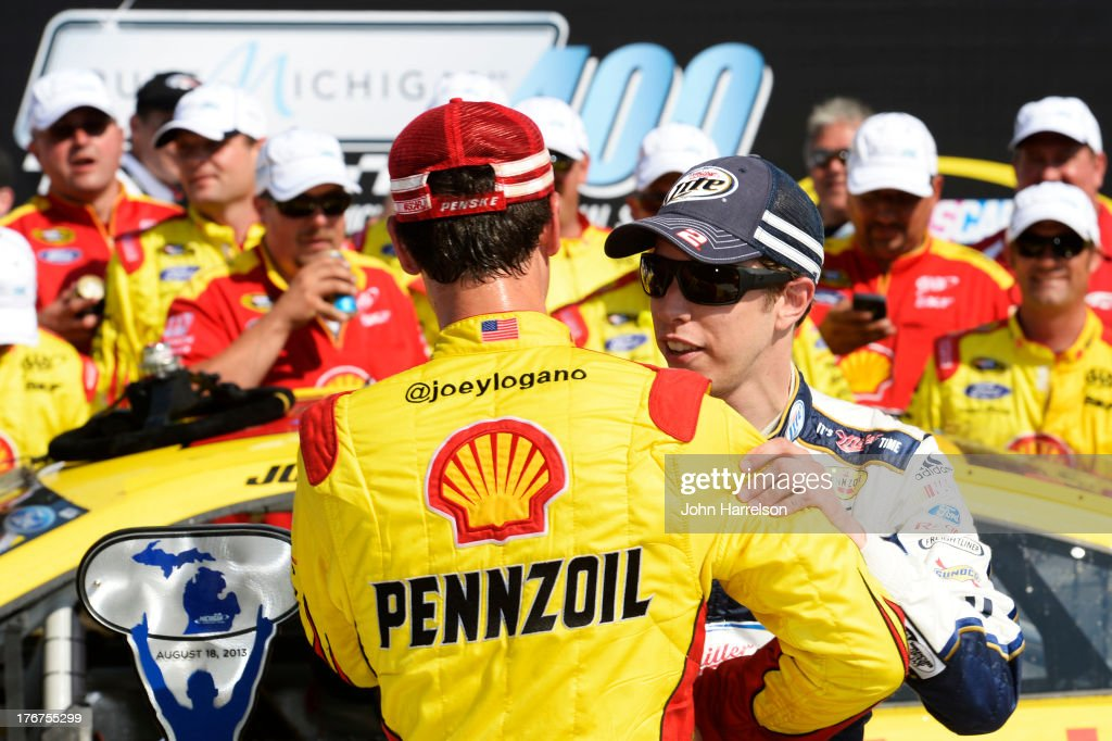 Joey Logano, driver of the #22 Shell-Pennzoil Ford, celebrates with Brad Keselowski, driver of the #2 Miller Lite / Luke Bryan Ford, in Victory Lane after winning the NASCAR Sprint Cup Series 44th Annual Pure Michigan 400 at Michigan International Speedway on August 18, 2013 in Brooklyn, Michigan.