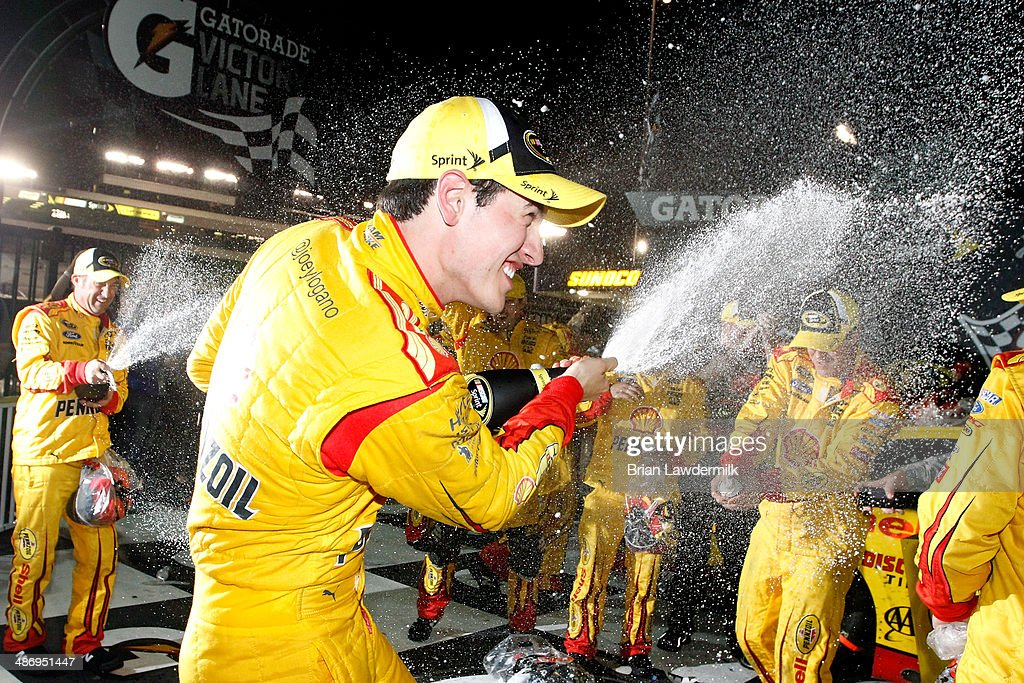 Joey Logano, driver of the #22 Shell-Pennzoil Ford, celebrates with champagne in Victory Lane after winning during the NASCAR Sprint Cup Series Toyota Owners 400 at Richmond International Raceway on April 26, 2014 in Richmond, Virginia.