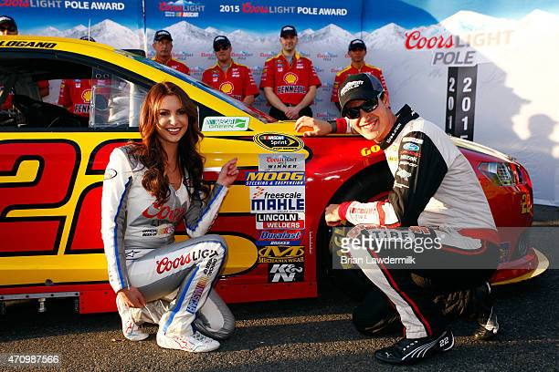 Joey Logano driver of the ShellPennzoil Ford celebrates with Miss Coors Light Amanda Mertz after winning the Coors Light Pole Award for the NASCAR...
