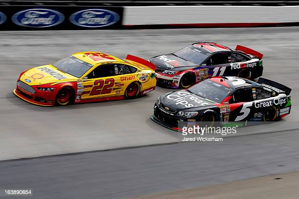 Joey Logano driver of the ShellPennzoil Ford races Denny Hamlin driver of the FedEx Freight Toyota and Kasey Kahne driver of the Great Clips...
