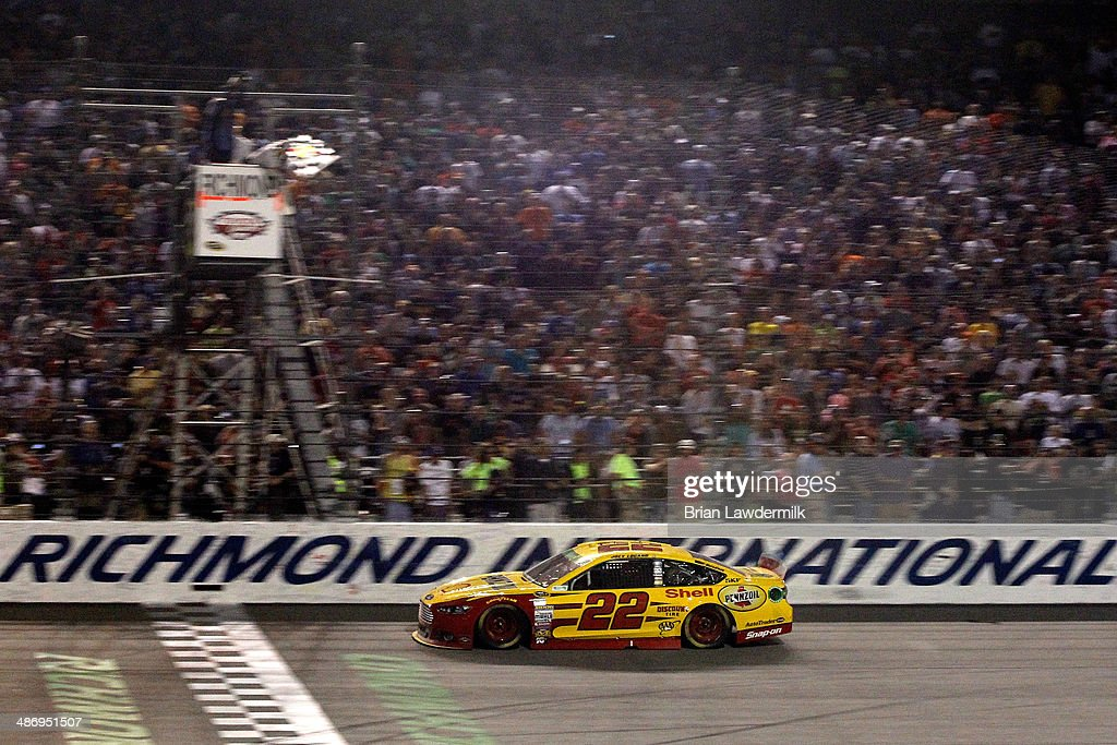 Joey Logano, driver of the #22 Shell-Pennzoil Ford, races to the checkered flag during the NASCAR Sprint Cup Series Toyota Owners 400 at Richmond International Raceway on April 26, 2014 in Richmond, Virginia.