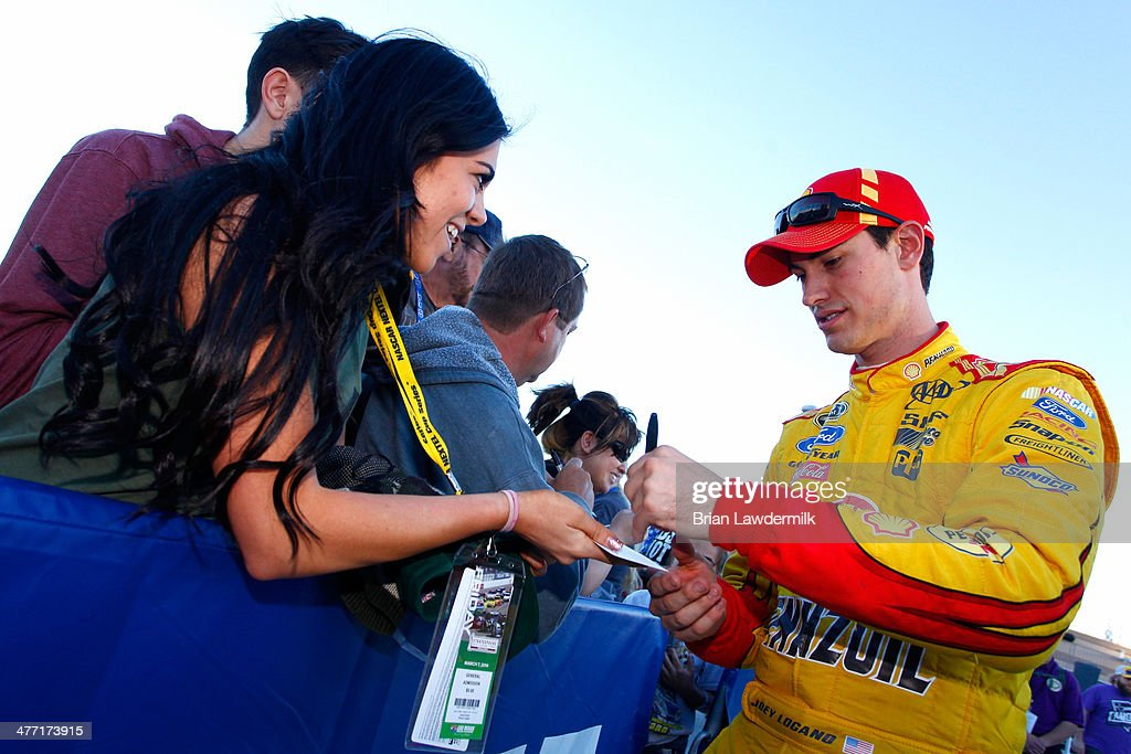 Joey Logano, driver of the #22 Shell-Pennzoil Ford, signs autographs for fans during qualifying for the NASCAR Sprint Cup Series Kobalt 400 at Las Vegas Motor Speedway on March 7, 2014 in Las Vegas, Nevada.