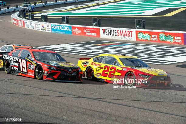 Joey Logano, driver of the Team Penske Shell Pennzoil Ford Mustang, leads Martin Truex Jr., driver of the Joe Gibbs Racing Bass Pro Shops Toyota...