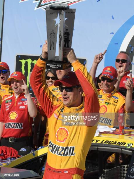 Joey Logano Team Penske Ford Fusion Shell Pennzoil hoists the winner's trophy in Victory Lane after winning the Monster Energy Cup Series 49th Annual...