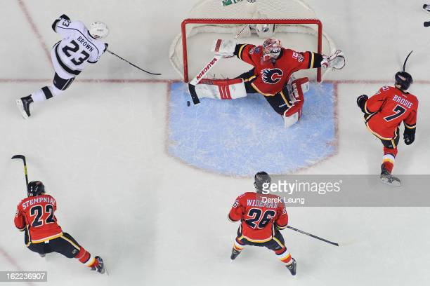 Joey MacDonald of the Calgary Flames stops the shot of Dustin Brown of the Los Angeles Kings during an NHL game at Scotiabank Saddledome on February...
