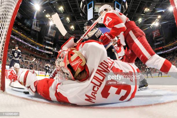 Joey MacDonald of the Detroit Red Wings covers up a loose puck before Derick Brassard of the Columbus Blue Jackets is able to get to it during the...