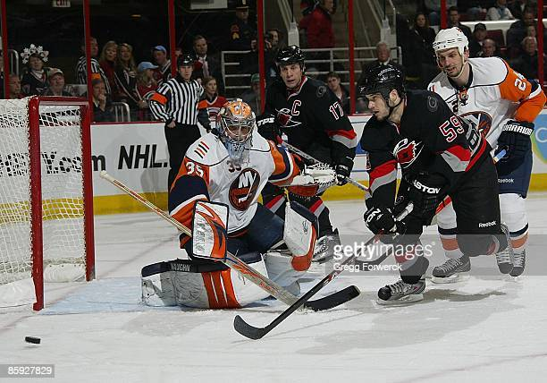 Joey MacDonald of the New York Islanders deflects the puck to make a save during a NHL game against the Carolina Hurricanes on April 7, 2009 at RBC...