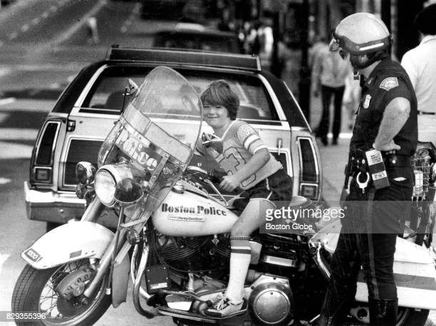 Joey Navis tries out the seat on Boston Police officer John Donovan's motorcycle on Broadway Street in South Boston on Sep 14 1981