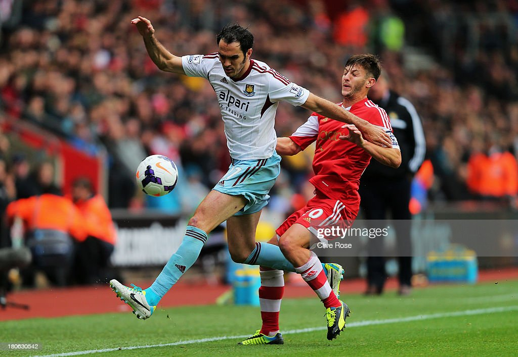 Joey O'Brien of West Ham is challenged by Adam Lallana of Southampton during the Barclays Premier League match between Southampton and West Ham United at St Mary's Stadium on September 15, 2013 in Southampton, England.