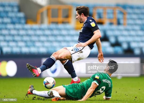Joey Pelupessy of Sheffield Wednesday tackles Ryan Leonard of Millwall FC during the Sky Bet Championship match between Millwall and Sheffield...