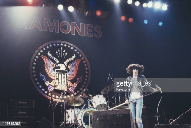 Joey Ramone singer with US punk band the Ramones on stage during a live concert performance by the band with drummer Tommy Ramone in the background...