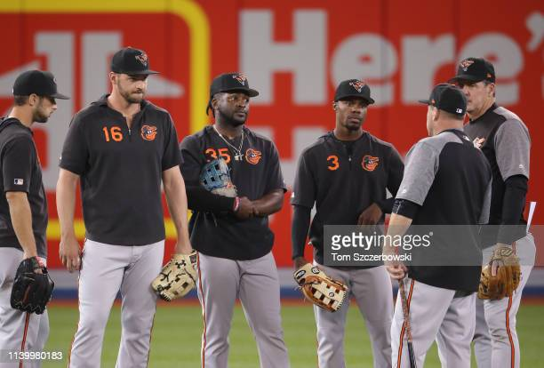 Joey Rickard of the Baltimore Orioles and Trey Mancini and Dwight Smith Jr #35 and Cedric Mullins listen to first base coach Arnie Beyeler and...