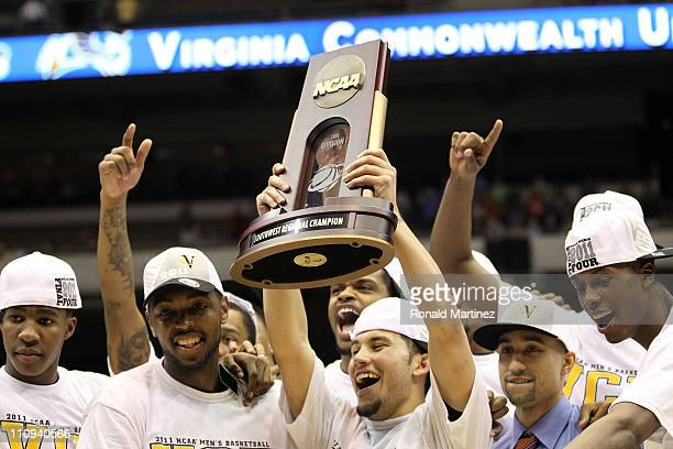 Joey Rodriguez of the Virginia Commonwealth Rams holds up the trophy after defeating the Kansas Jayhawks during the southwest regional final of the...