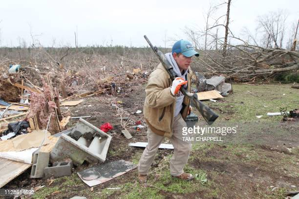 Joey Roush carries a rifle and other items from his mother's home after it was destroyed in a tornado in Beauregard Alabama on March 4 2019 Rescuers...
