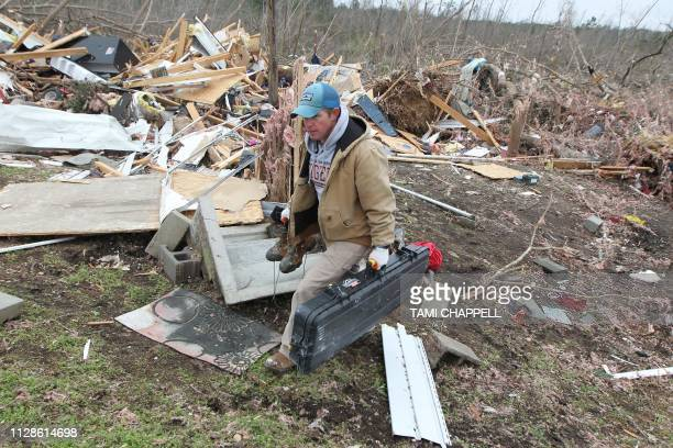 Joey Roush carries items from his mother's home after it was destroyed in a tornado in Beauregard Alabama on March 4 2019 Rescuers in Alabama were...