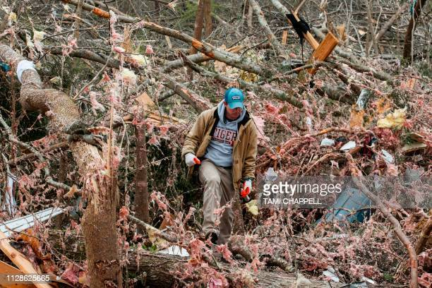 Joey Roush walks through debris March 4 2019 at his mother's home after it was destroyed in a tornado in Beauregard Alabama Rescuers in Alabama...