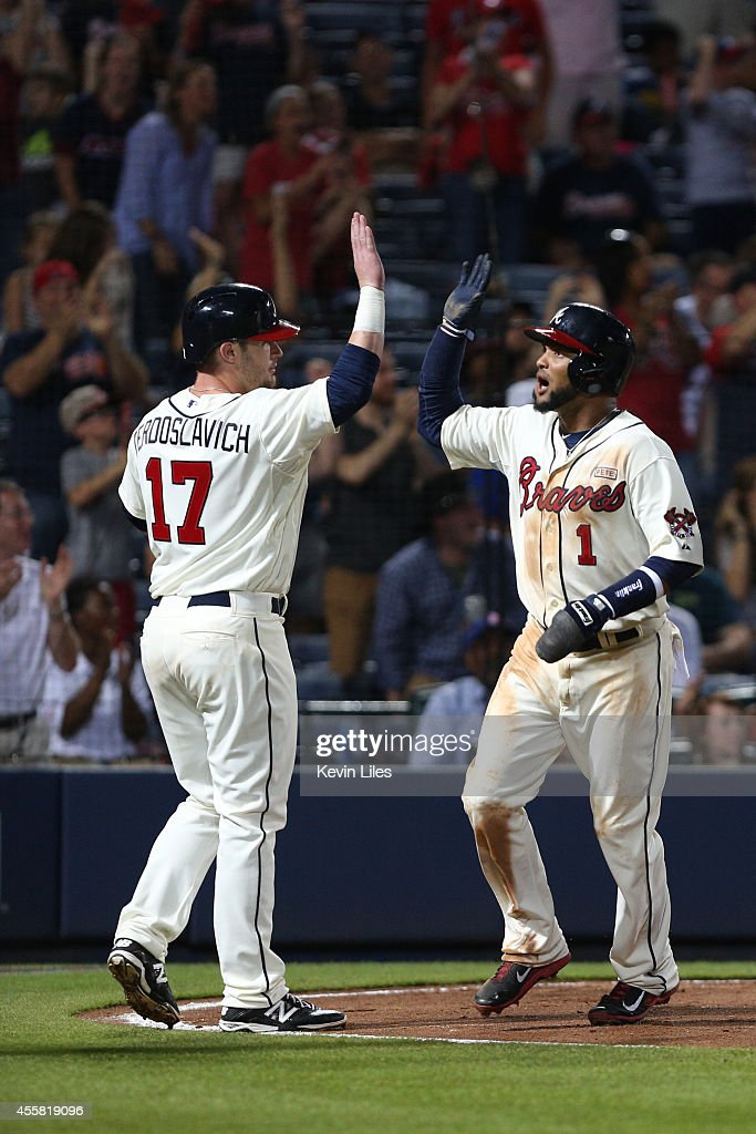 Joey Terdoslavich #17 of the Atlanta Braves and Emilio Bonifacio #1 celebrate after they both scored during the 8th inning against the New York Mets at Turner Field on September 20, 2014 in Atlanta, Georgia.