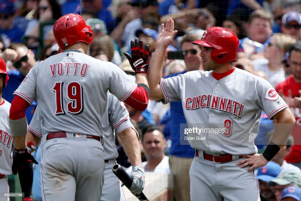 Joey Votto #19 and Jose Peraza #9 of the Cincinnati Reds celebrate after Votto hit a home run in the second inning against the Chicago Cubs at Wrigley Field on August 17, 2017 in Chicago, Illinois.