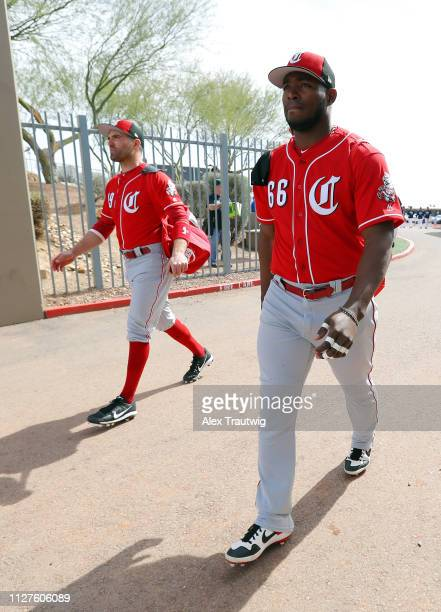 Joey Votto and Yasiel Puig of the Cincinnati Reds walk to the field ahead of a Spring Training game against and the Seattle Mariners on Monday...