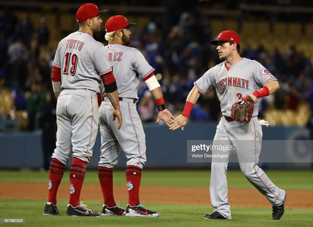 Joey Votto #19, Eugenio Suarez #7 and Scooter Gennett #3 of the Cincinnati Reds celebrate in the infield grass their 5-3 win against the Los Angeles Dodgers at Dodger Stadium on May 12, 2018 in Los Angeles, California. The Reds defeated the Dodgers 5-3.