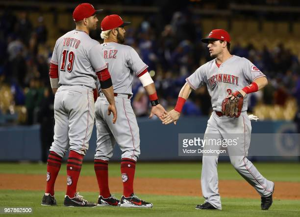 Joey Votto Eugenio Suarez and Scooter Gennett of the Cincinnati Reds celebrate in the infield grass their 53 win against the Los Angeles Dodgers at...