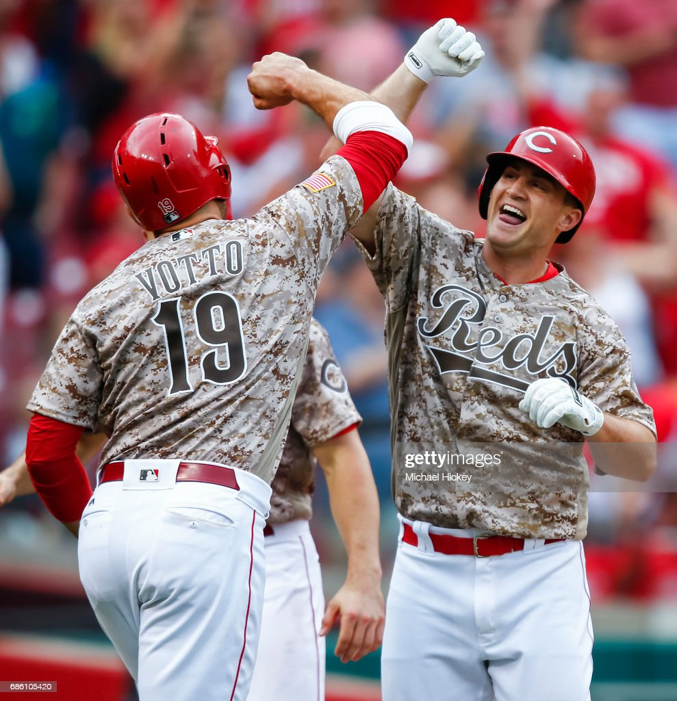 Joey Votto #20 of the Cincinnati Reds and Scott Schebler #43 of the Cincinnati Reds celebrate after Schebler hit a three-run homer in the sixth inning to go ahead of the Colorado Rockies at Great American Ball Park on May 20, 2017 in Cincinnati, Ohio.