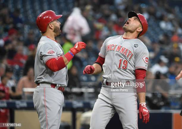 Joey Votto of the Cincinnati Reds celebrates with Eugenio Suarez after hitting a solo home run during the first inning of a baseball game against the...