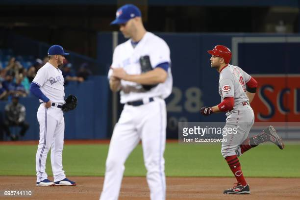 Joey Votto of the Cincinnati Reds circles the bases after hitting a solo home run in the first inning during MLB game action as JA Happ of the...