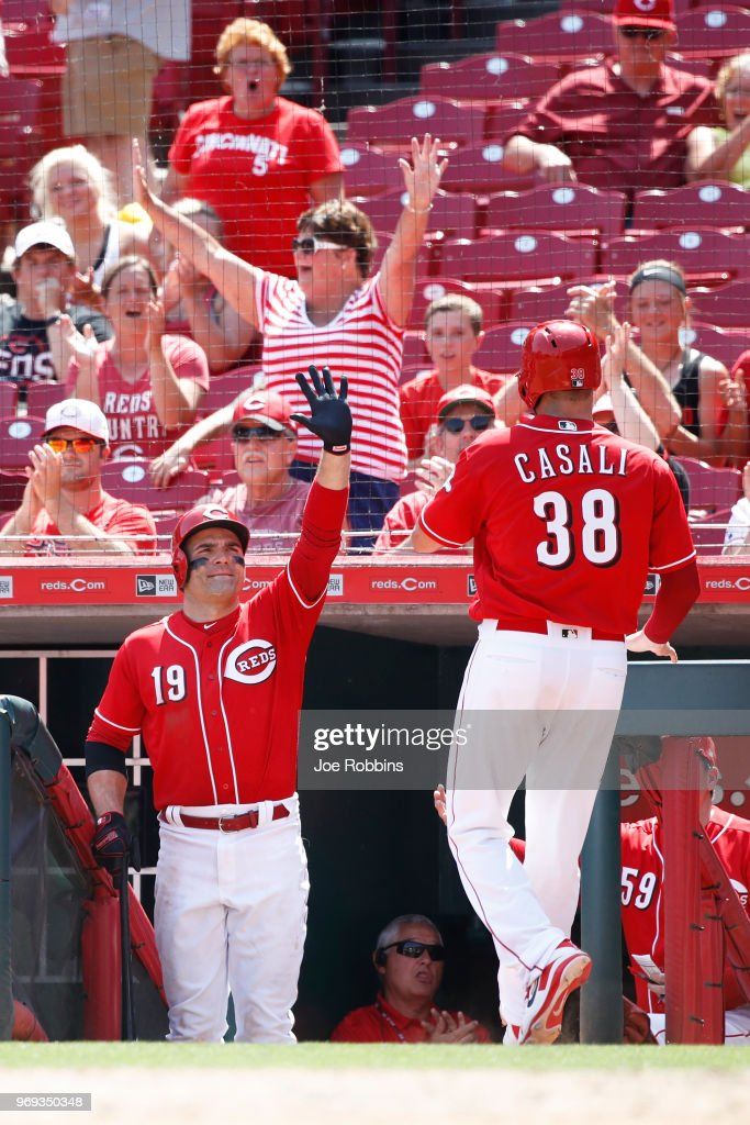Joey Votto #19 of the Cincinnati Reds congratulates Curt Casali #38 after he scored on a wild pitch by Wade Davis of the Colorado Rockies to tie the game in the ninth inning at Great American Ball Park on June 7, 2018 in Cincinnati, Ohio. The Reds won 7-5 in 13 innings.
