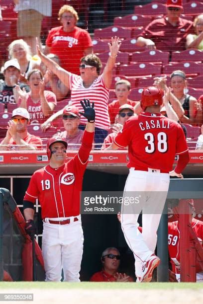 Joey Votto of the Cincinnati Reds congratulates Curt Casali after he scored on a wild pitch by Wade Davis of the Colorado Rockies to tie the game in...