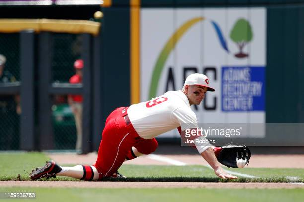 Joey Votto of the Cincinnati Reds dives to field a ground ball in the first inning against the Chicago Cubs at Great American Ball Park on June 30...