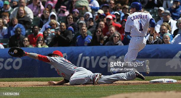 Joey Votto of the Cincinnati Reds dives to make a catch on a late throw as Tony Campana of the Chicago Cubs crosses first base at Wrigley Field on...