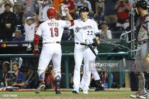 Joey Votto of the Cincinnati Reds is congratulated by Christian Yelich of the Milwaukee Brewers after hitting a home run in the 10th inning during...