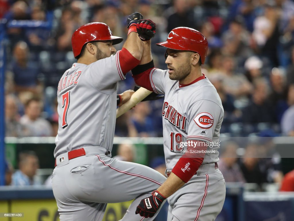 Joey Votto #19 of the Cincinnati Reds is congratulated by Eugenio Suarez #7 after hitting a solo home run in the first inning during MLB game action against the Toronto Blue Jays at Rogers Centre on May 30, 2017 in Toronto, Canada.