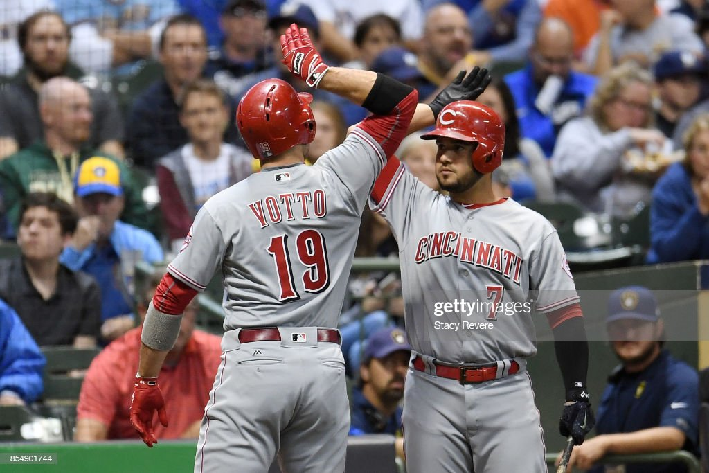 Joey Votto #19 of the Cincinnati Reds is congratulated by Eugenio Suarez #7 after a solo home run against the Milwaukee Brewers during the first inning of a game Miller Park on September 27, 2017 in Milwaukee, Wisconsin.