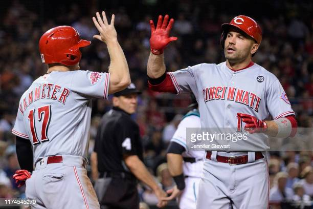 Joey Votto of the Cincinnati Reds is congratulated by Josh VanMeter after hitting a two run home run in the third inning of the MLB game against the...
