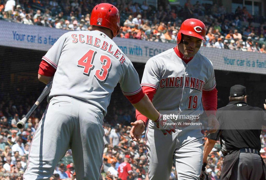 Joey Votto #19 of the Cincinnati Reds is congratulated by Scott Schebler #43 after Votto scored on a pass ball by catcher Nick Hundley #5 of the San Francisco Giants in the top of the fifth inning at AT&T Park on May 16, 2018 in San Francisco, California.