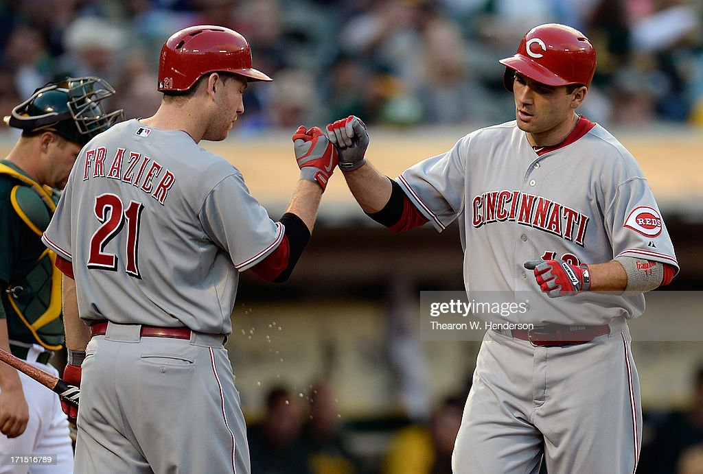 Joey Votto #19 of the Cincinnati Reds is congratulated by Todd Frazier #21 after Votto hit a solo home run in the fourth inning against the Oakland Athletics at O.co Coliseum on June 25, 2013 in Oakland, California.