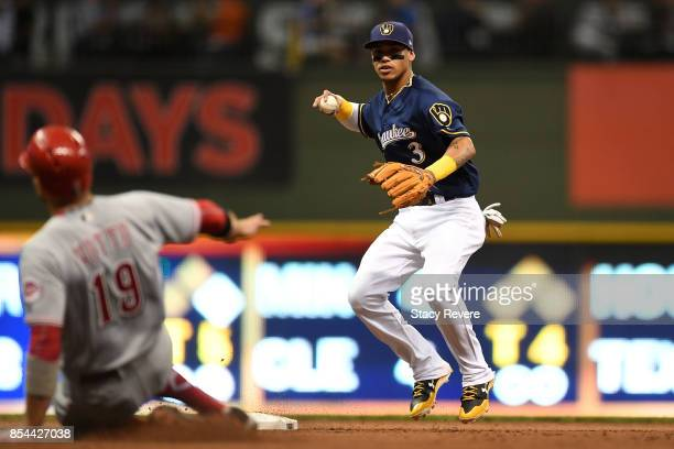 Joey Votto of the Cincinnati Reds is forced out at second base as Orlando Arcia of the Milwaukee Brewers turns a double play during the third inning...