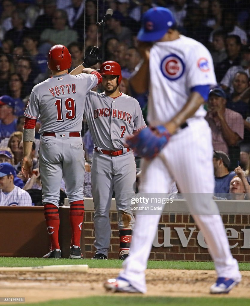 Joey Votto #19 of the Cincinnati Reds is greeted by Eugenio Suarez #7 after scoring a run in the 8th inning as Pedro Strop #46 of the Chicago Cubs walks back to the mound at Wrigley Field on August 15, 2017 in Chicago, Illinois.
