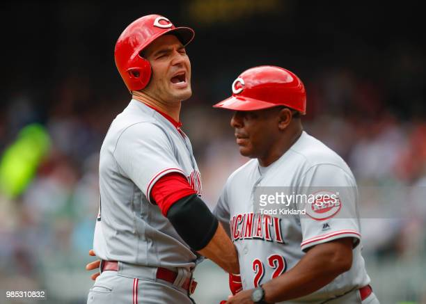 Joey Votto of the Cincinnati Reds is restrained by third base coach Billy Hatcher as he is ejected from the game in the first inning of an MLB game...