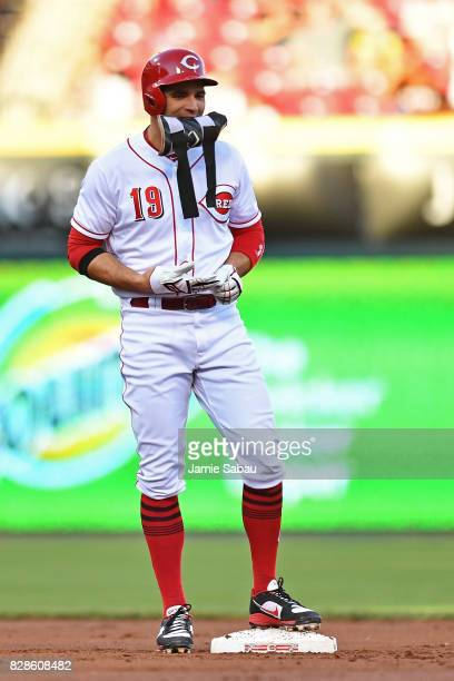Joey Votto of the Cincinnati Reds removes his pad and gloves after hitting a double in the first inning against the San Diego Padres at Great...