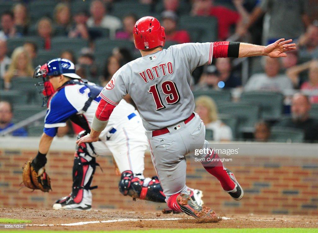 Joey Votto #19 of the Cincinnati Reds scores on a seventh inning sacrifice fly against Kurt Suzuki #24 of the Atlanta Braves at SunTrust Park on August 19, 2017 in Atlanta, Georgia.