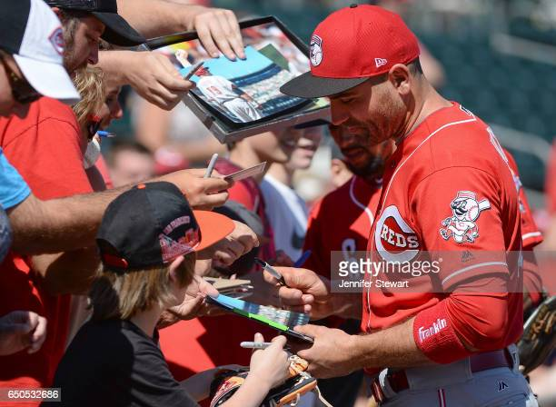 Joey Votto of the Cincinnati Reds signs autographs for fans prior to the spring training game against the Oakland Athletics at HoHoKam Stadium on...